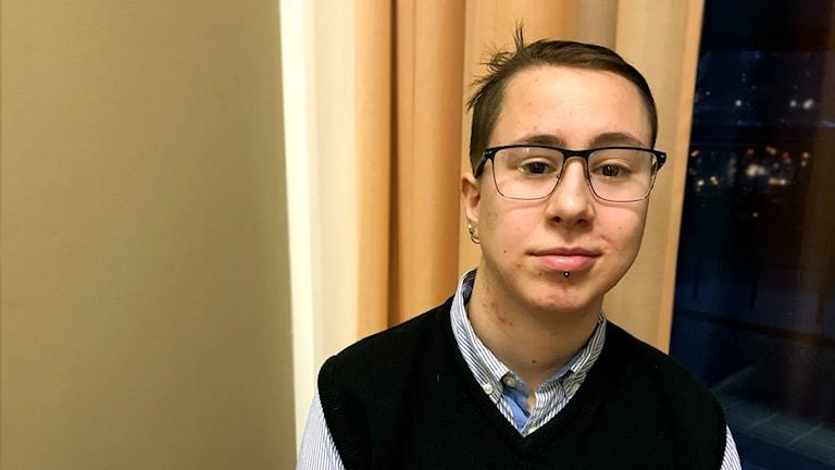 Porträttbild av en ung man med brunt hår och glasögon.