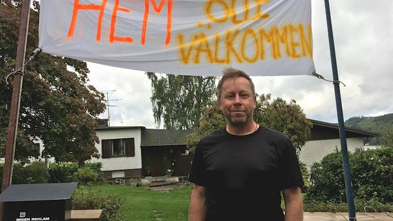 Olle Svalander framför en banderoll med texten Välkommen hem Olle.