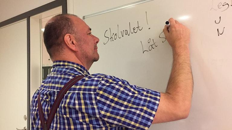 """Joakim Cannerfors klädd i rutig skjorta och hängslen skriver """"Skolvalet! Låt stå!"""" på en whiteboard."""