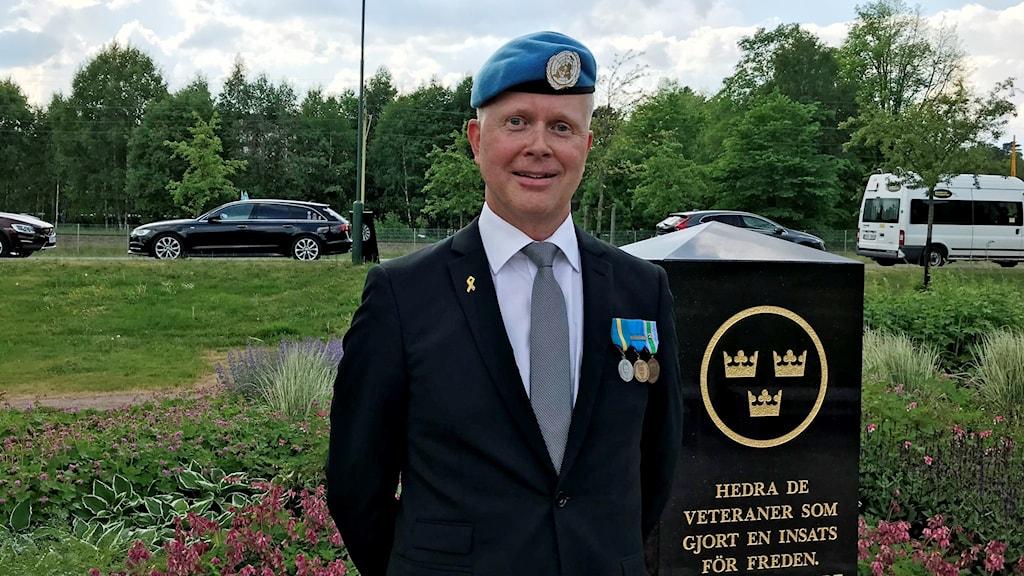 Johan Nolén i blå basker framför minnessten