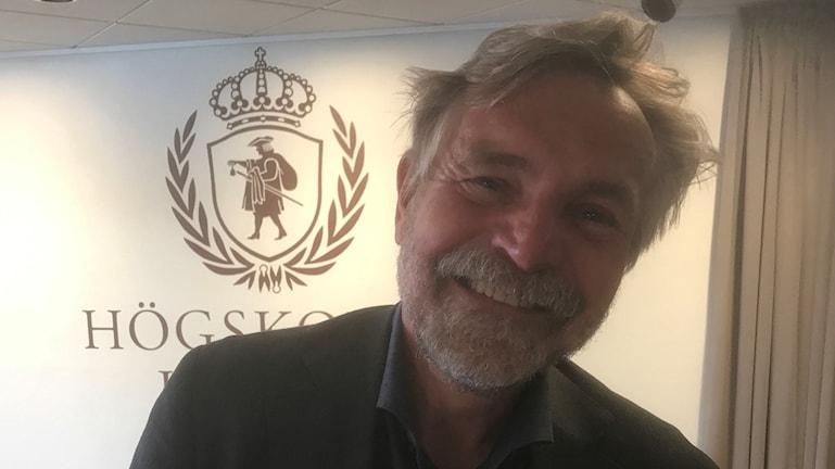 Björn Brorström, rektor på Högskolan i Borås är glad. han ler mot kameran med huvudet på sned.