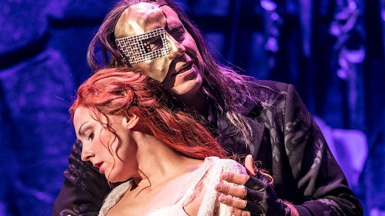 En man i mask håller om en kvinna med långt rött hår