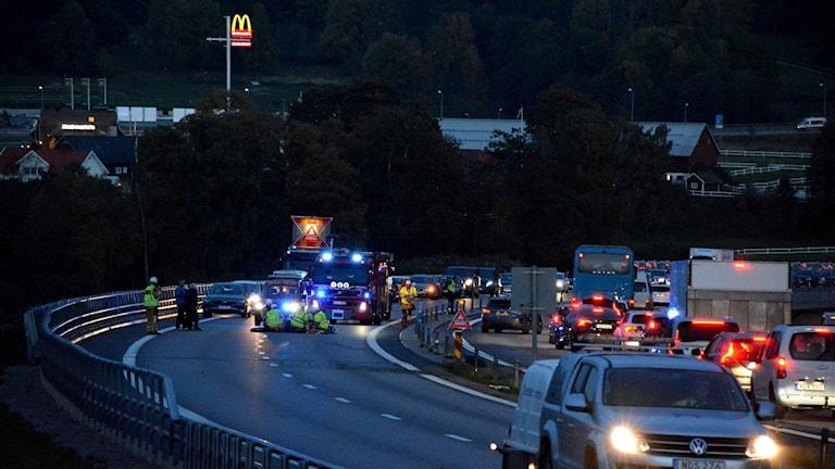 Bilar i kö och polis och räddningspersonal vid väg efter olycka