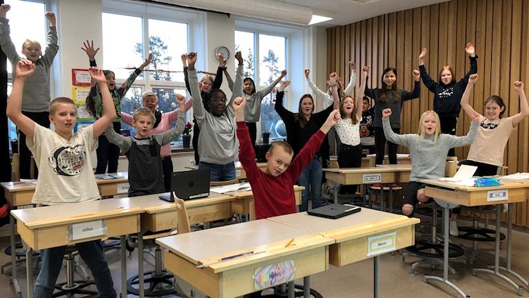 En glad skolklass som sträcker armarna i luften.