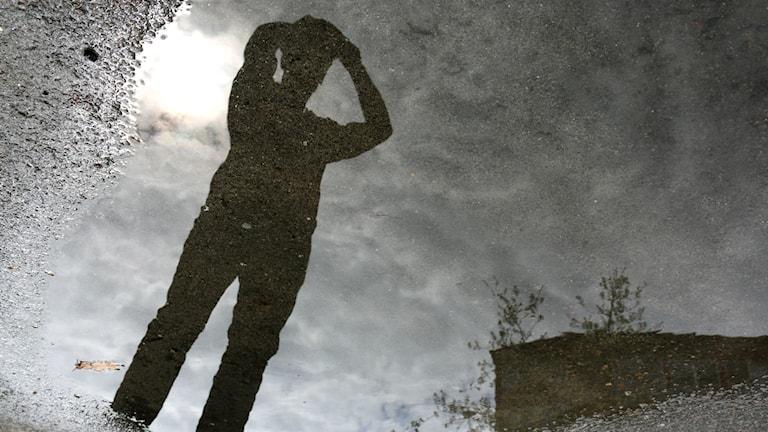 En persons silhuett speglas i en vattenpöl mot en grå himmel. Personen tar sig för huvudet med båda händerna. Till höger skymtar en byggnad i bakgrunden.