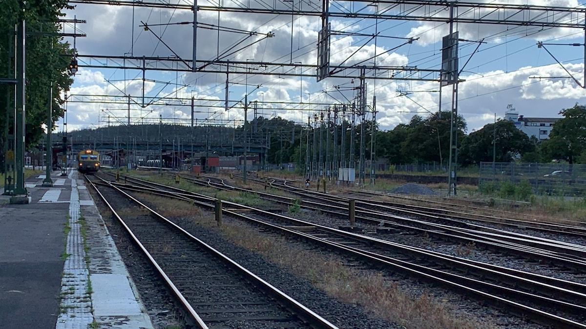 Den långa perrongen på spår 1 sträcker sig brevid järnvägspåret, längre bort står ett tåg. Flera järnvägspår med växlar mellan. Mot himlen finns flera kotaktledningar och elstolpar i stål. Den blå himlen döljs mestadels av moln.