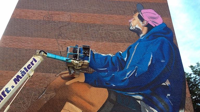 En konstnär målar en stor målning på en tegelvägg
