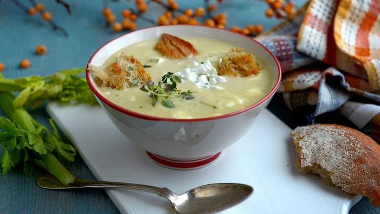 en skål med soppa, en sked och en bit bröd