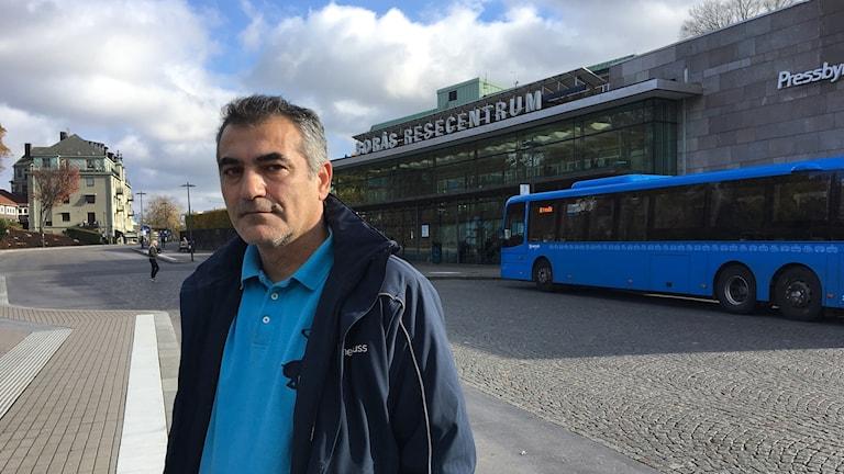 Mike SHarro står på Borås Resecentrum, bakom honom syns kullerstensgator, ingången till Borås Resecentrum där det står en blå Västtrafikbuss framför.