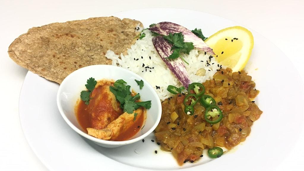 En tallrik med grönsaksröra, ris, plattbröd och en liten skål med ett tillbehör.