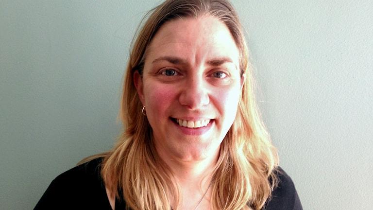 Anna Troberg står mitt framför kameran mot en vit vägg och tittar leende in i kameran.