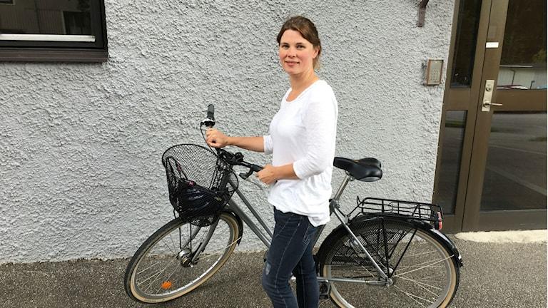 Clara Hyltbäck står framför en cykel.