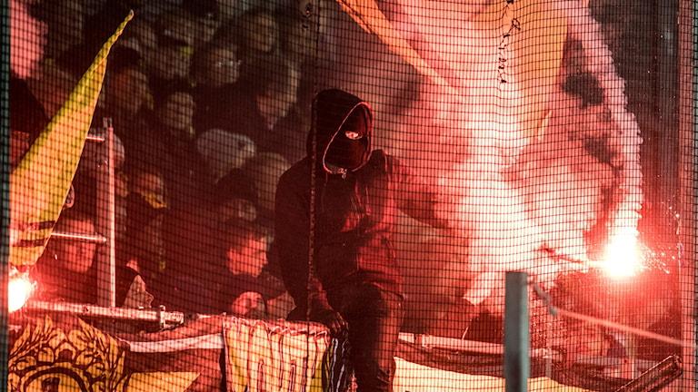 En maskerad Elfsborgssupporter sitter på räcket med en blossande bengal i handen.