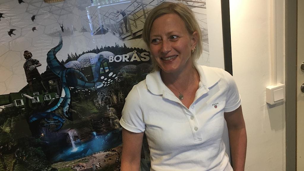 Kvinna i vit pikétröja framför affish med namnet Borås.