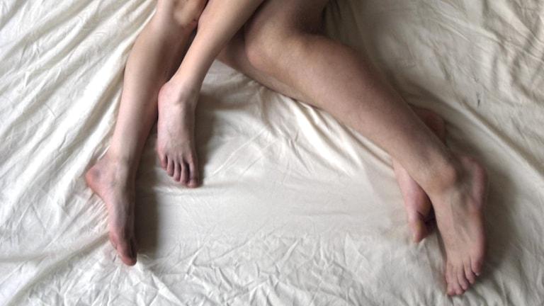 Benen på ett naket par i en säng.