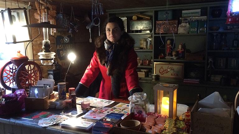 En kvinna står i röd kappa bakom disken i en gammal handelsbod