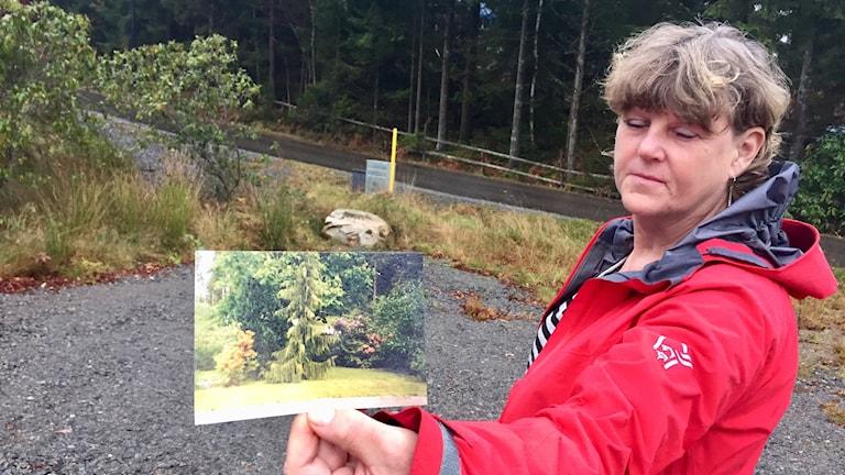 Kvinna i röd jacka håller upp ett fotografi som visar hur hennes trädgård såg ut innan vattnet från grannens tomt började tränga in i hennes trädgård.