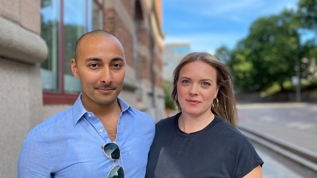 En man med blå skjorta och en kvinna i mörkblå t-shirt står bredvid varandra på en trottoar.