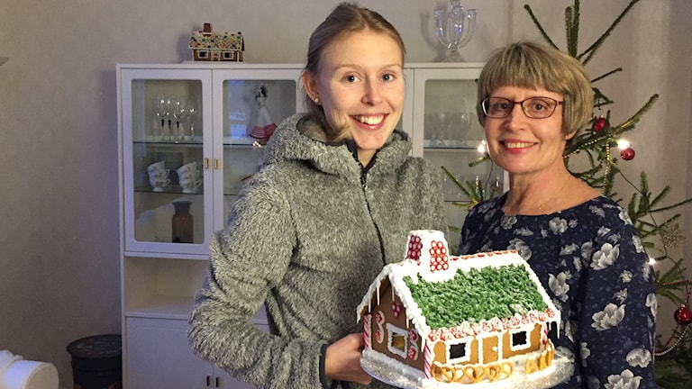 Amanda Fransson ihop med glad mamma hållandes i pepparkakshus