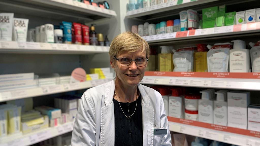 En kvinna står i sin vita farmaceut-rock framför en hylla medicin på Apoteket