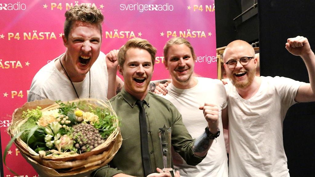 Fyra bandmedlemmar med blommor och pokal.
