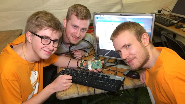 Tre unga män håller en enkeldator