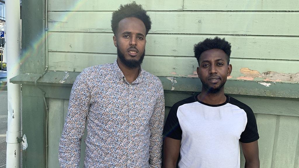 Hamse och Abshir står framför en grön vägg