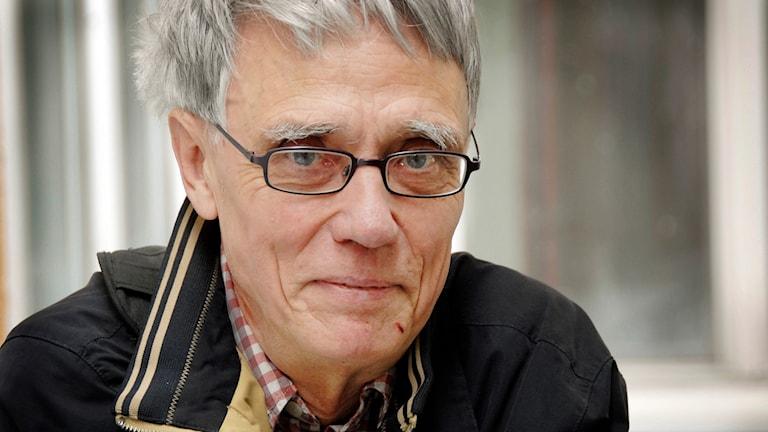 En äldre man med grått hår och rektangulära glasögon.