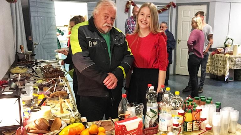 En man och en kvinna står framför ett bord med julmat och dricka
