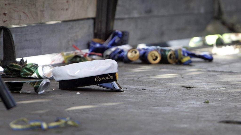 En vit studentmössa ligger på golvet framför ett staket. Bredvid och bakom mössan syns tomma, ihopskrynklade ölburkar och blågula serpentiner.