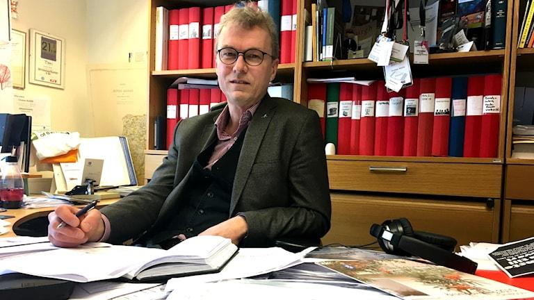 Christian bonfré sitter iklädd grå kavaj vid sitt skrivbord som är fyllt med papper och mappar. Han har en penna i högra handen som ligger på bordet och den andra vilar på armstödet på stolen. Bakom honom syns ännu mera papper och en bokhylla med en massa röda pärmar.