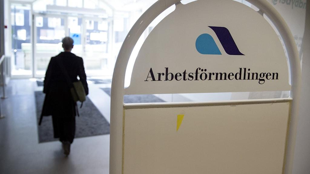 Arbetsförmedlingens logotyp på en skylt i en entré och ryggen på en människa som går ut ur bilden.