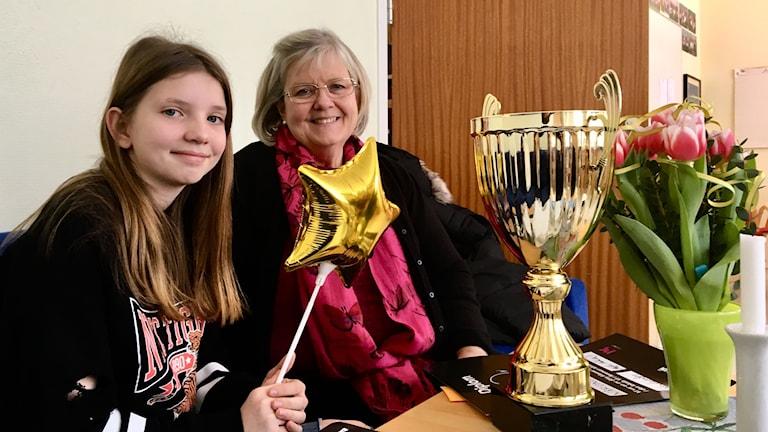 Lisa Karlsson sitter till vänster i en soffa och håller i en stjärnformad, guldig ballong. Vid hennes sida sitter läraren Maria Utter Fredin. På bordet framför dem står en guldig pokal och en bukett tulpaner.