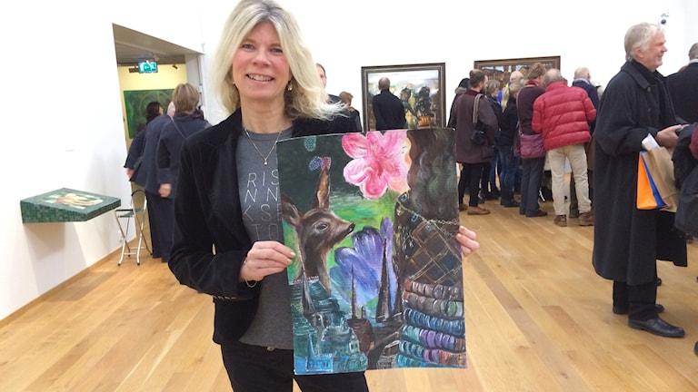 En kvinna håller upp en tavla hon målat