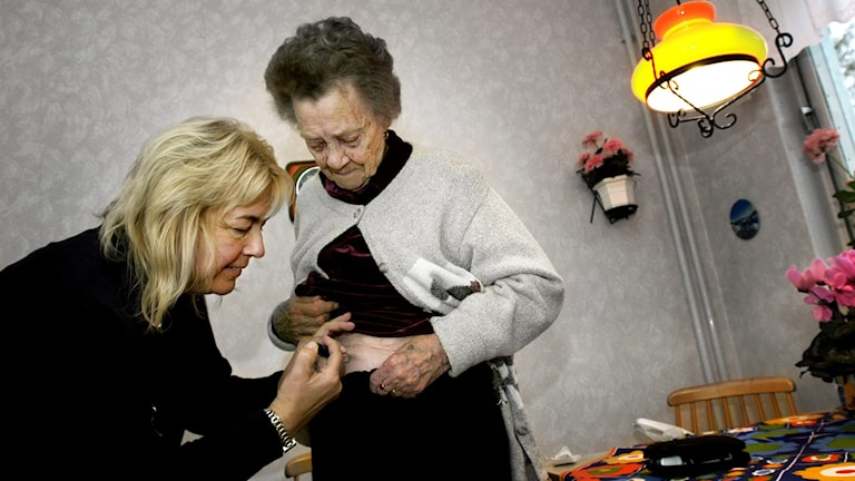 Kvinna får hjälp med spruta.