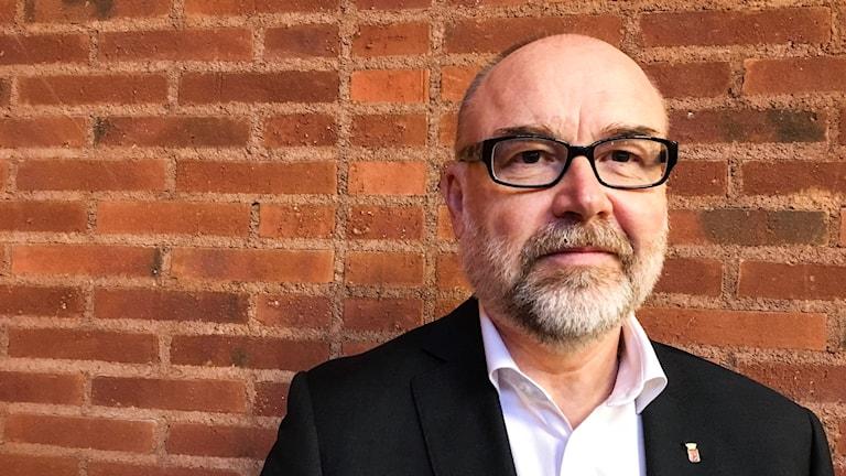 Svante Stomberg, kommunchef i Borås, framför en tegelvägg.