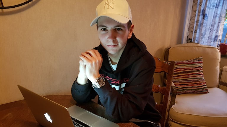 Ung kille med svart tröja och vit keps tittar in i kameran och sitter framför en bärbar dator.