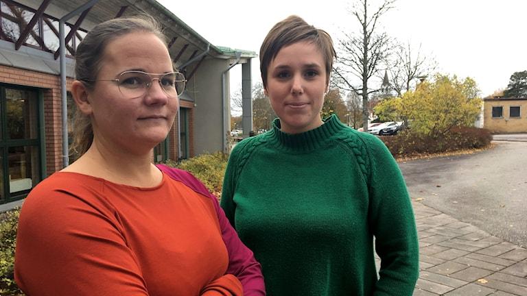 Carolina Nielsen i orange tröja och Malin Kaas i grön tröja står utanför Tranemo Gymnasieskola. I bakgrunden syns några gulnande buskar och träd.