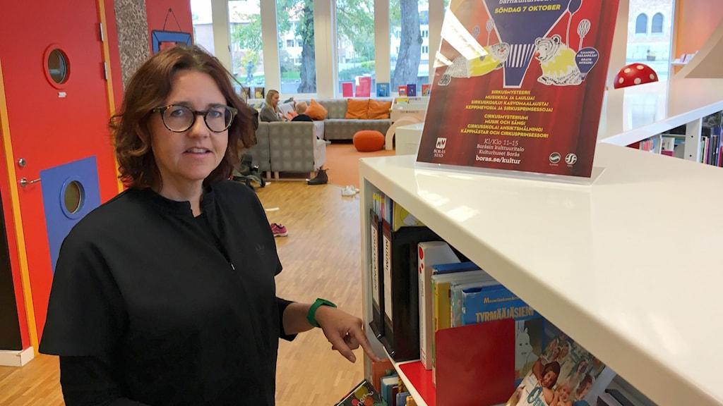 Åsa-Marie Berg Levinsson vid en bokhylla i biblioteket.
