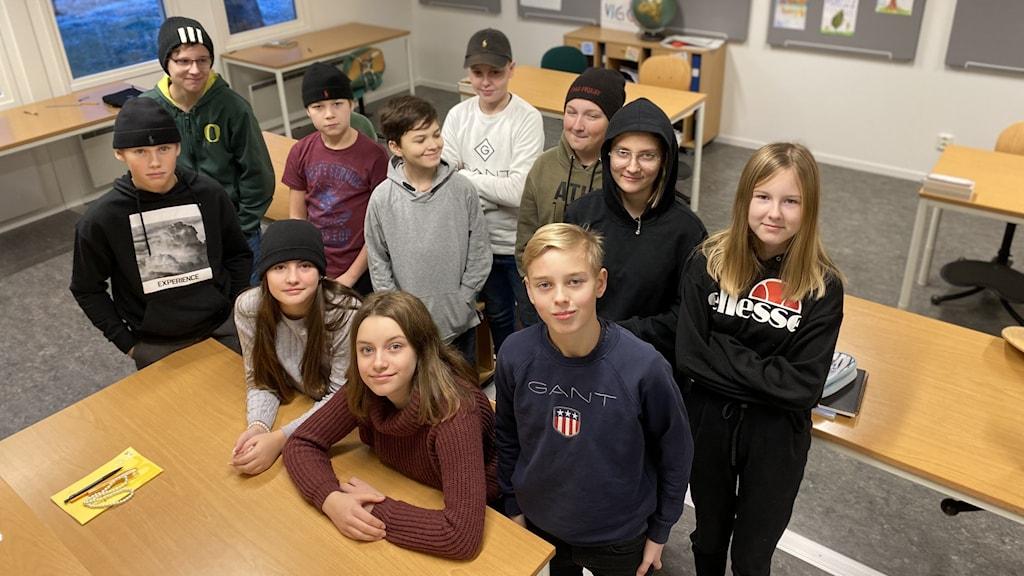 Barnen står och sitter i en klunga i klassrummet