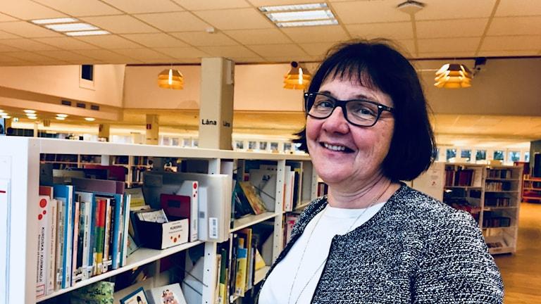 Åsa Hedberg Karlsson står till höger i bild och ler mot kameran, bakom henne syns bibliotekets vita hyllor fyllda med böcker.