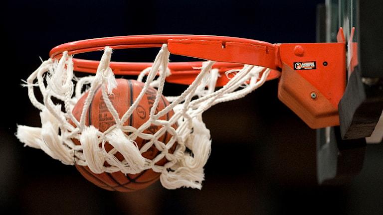 En boll skjuts ner i en basketkorg.