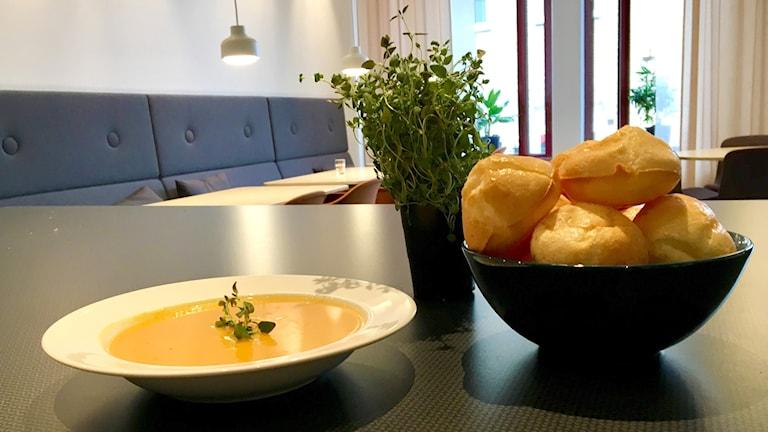 En tallrik med pumpasoppa, en skål med ostbull, en kruka timjan på ett svart bord