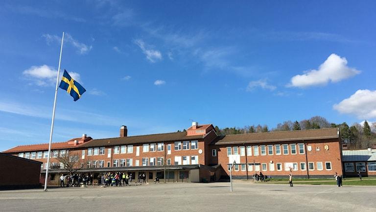 Ängskolan i Skene sett från distans. En röd tegelbyggnad med vita fönster, i förgrunden skolgården, en stor asfaltsplan. Till vänster en flaggstång med Sveriges flagg på halv stång. Strax nedanför den syns en grupp elever och lärare från skolan. Bakom skolbyggnaden en klarblå himmel med några få, vita moln.