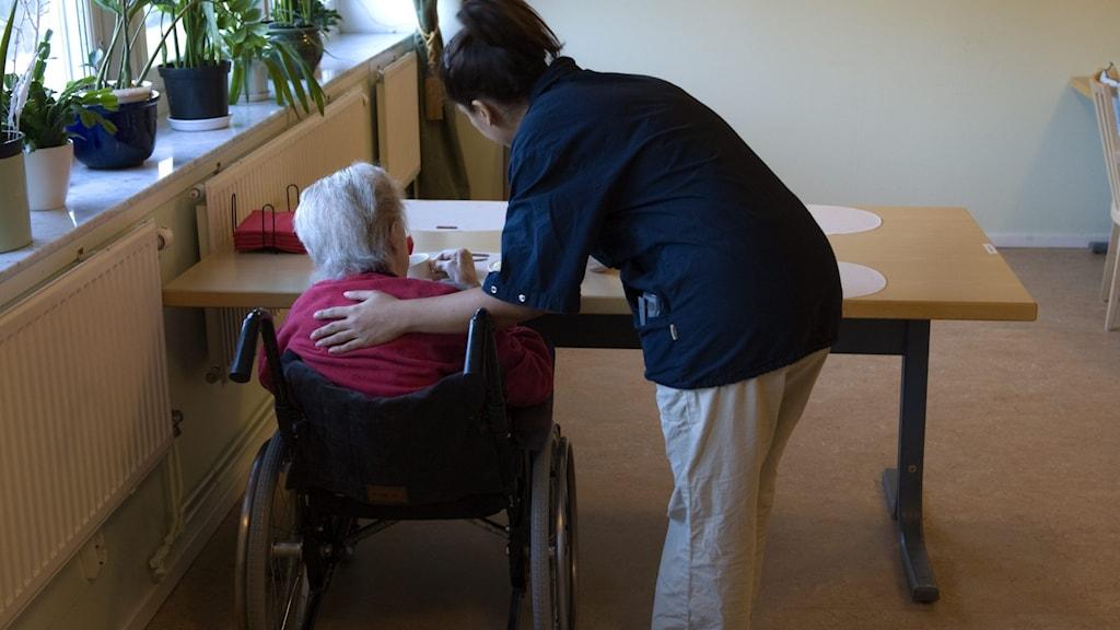 Kvinna håller äldre kvinna om ryggen.
