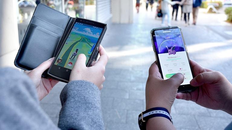 två personer håller var sin mobiltelefon och spelar Pokémon