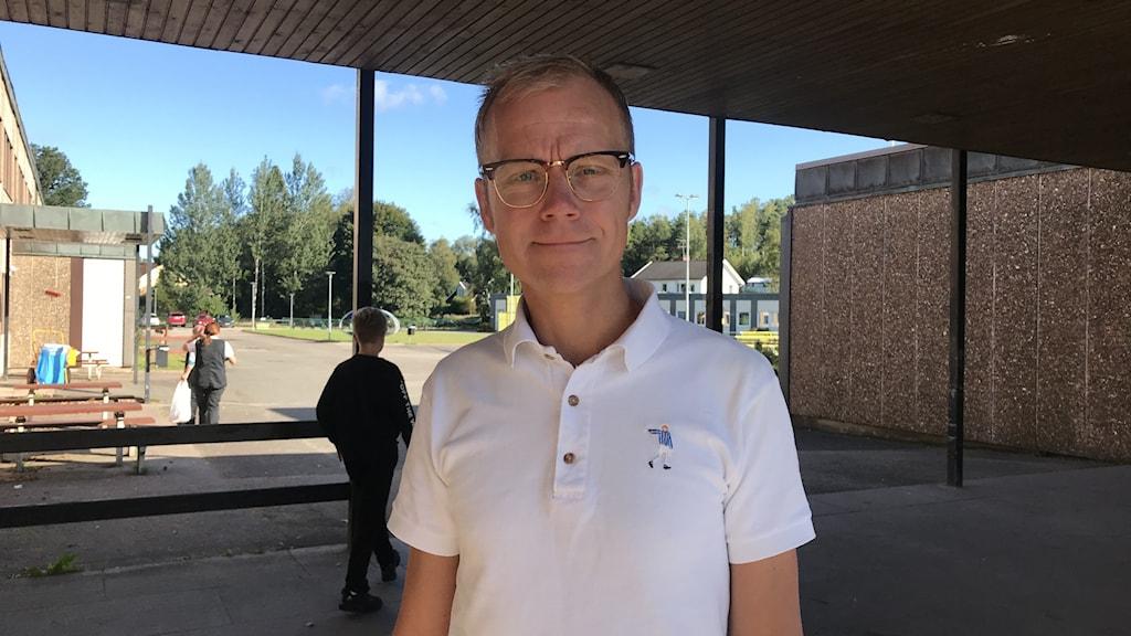 En man står på skolgården vid Sandgärdskolan.