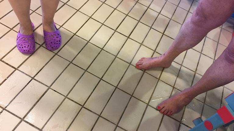 Bilden föreställer bara fötter i en simhall.