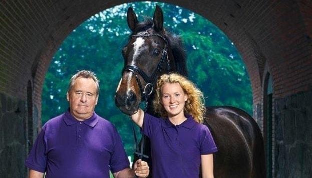 Två personer i lila tröja och en brun häst
