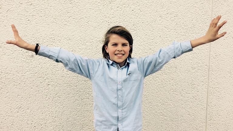 En pojke slår ut med armarna
